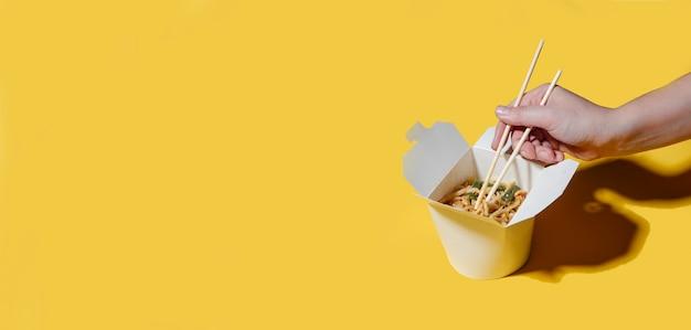 Il concetto di consegna del cibo su uno sfondo giallo tagliatelle in scatole