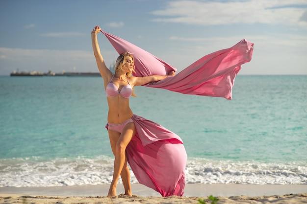 Concetto di libertà e felicità. donna felice sulla spiaggia in estate con seta rosa volante.