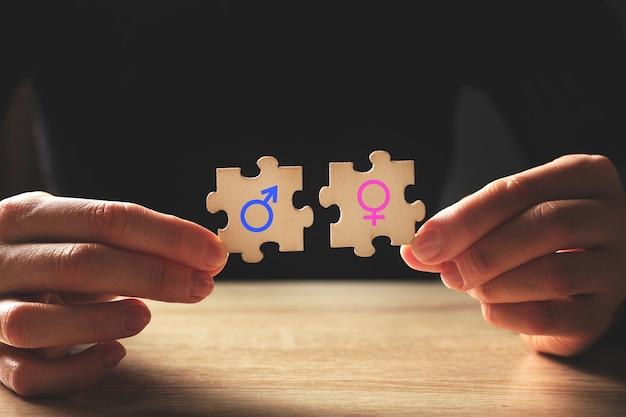 Concetto di compatibilità di genere con segni femminili e maschili sui puzzle.