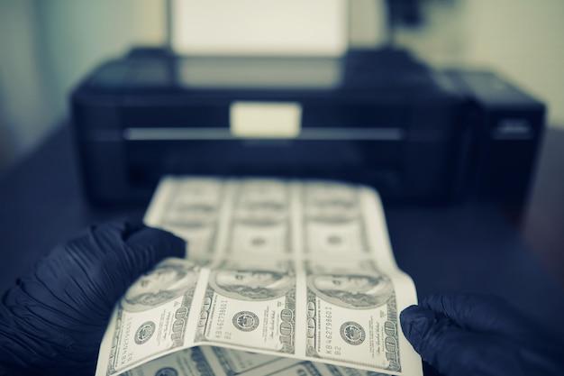 Il concetto di crisi economica globale. produzione illegale di dollari usa. stampa denaro sottoterra. stampare banconote da cento dollari da un criminale.