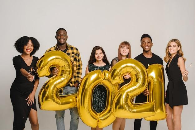 Concetto di felicità, celebrazione, risate e sorrisi. gruppo di festaioli che celebra l'arrivo del 2020
