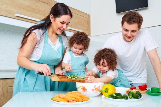 Il concetto di una famiglia felice ragazze gemelli madre padre e figlia gemelli vegitarianskuyu preparare i pasti in cucina felicità risate e sorrisi