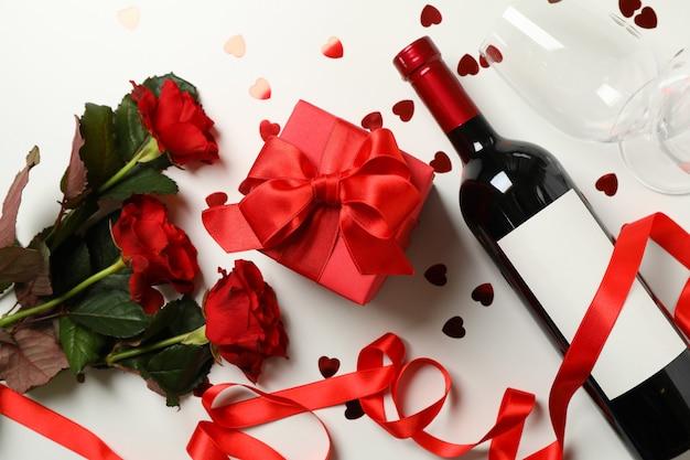 Concetto di buon san valentino con vino, rose e confezione regalo su sfondo bianco