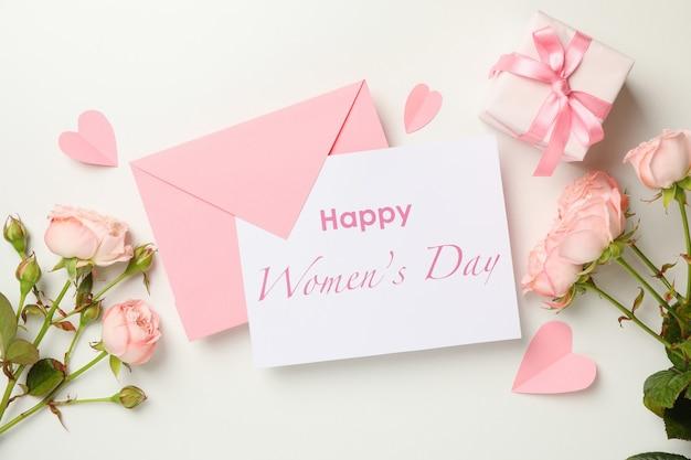 Concetto di giornata della donna felice con busta, rose e confezione regalo su sfondo bianco