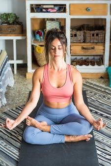 Concetto di anima e corpo sani vista ritagliata della donna americana sportiva medita sul materassino yoga facendo il gesto del mudra seduto nel loto dopo l'allenamento sportivo a casa