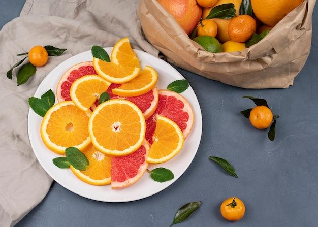 Concetto di mangiare sano, agrumi su un tavolo, arance mature a fette e pompelmo con un sacchetto di carta con arance, mandarini con foglie. foto ad alta risoluzione