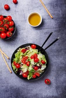 Concetto di cibo vegano sano. insalata con cetrioli, pomodori, insalata verde e cicoria