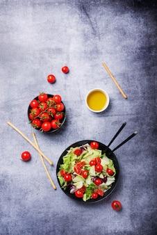 Concetto di cibo vegano sano. insalata di cetrioli, pomodori, insalata verde e cicoria