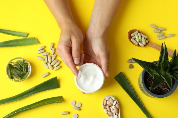 Concetto di pillole di erbe e cosmetici con aloe su sfondo giallo