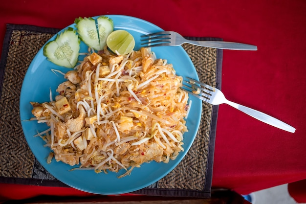 Concetto luna di miele in asia, amore, 14 febbraio, viaggio romantico. deliziosi spaghetti tailandesi tradizionali pad thai su un piatto, cetrioli nel cuore fermo e 2 forchette. vista dall'alto.