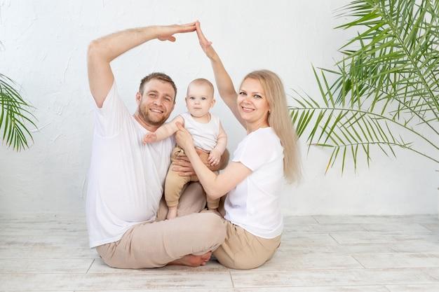 Il concetto di alloggio o mutui per una giovane famiglia. madre padre e bambino in una nuova casa con un tetto in una casa fuori mano