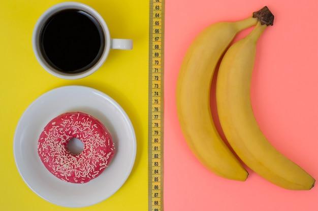 Concetto di cibo spazzatura vs frutta. appetitosa ciambella glassata con una tazza di caffè forte isolato su banane gialle e fresche isolate su rosa. metro a nastro tra i prodotti, vista dall'alto