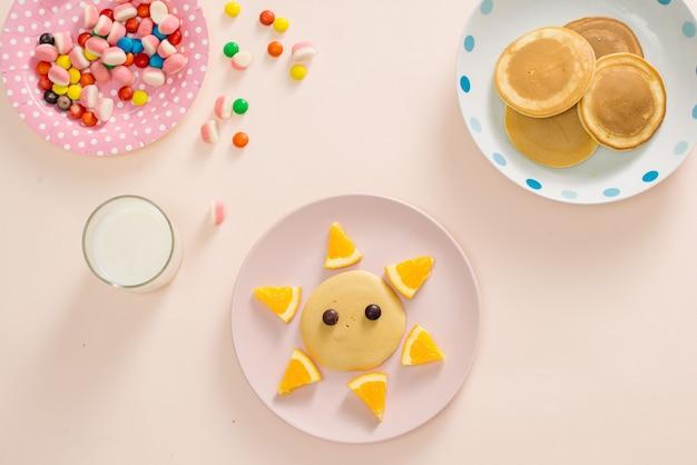 Concetto colazione per bambini con vista dall'alto di pancake su sfondo bianco