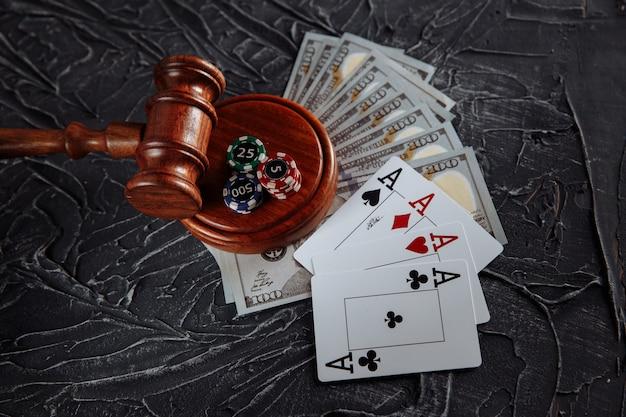 Concetto di regolamentazione giuridica del gioco d'azzardo, martelletto della giustizia sullo sfondo di un vecchio tavolo grigio.