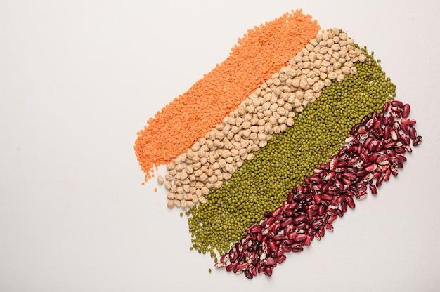 Concetto di poltiglia di legumi ceci lenticchie fagioli sul tavolo bianco proteine vegetali superficie vista dall'alto