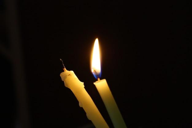 Concept una candela accesa accanto a una candela spenta