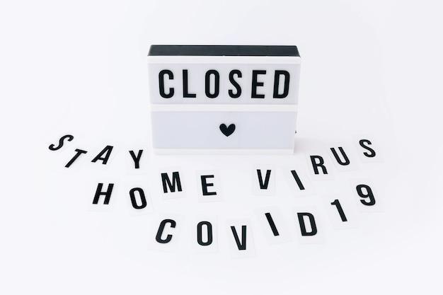 Concetto di blocco, covid 19. testo visualizzato nel lightbox e parole stay home, virus, covid-19 intorno al lightbox sul tavolo luminoso.