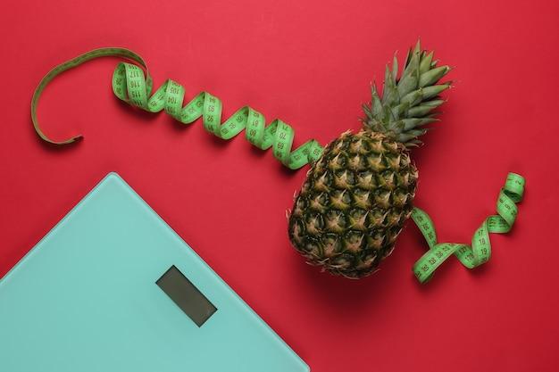 Il concetto di perdere peso. scale, ananas con nastro di misurazione su sfondo rosso. mangiare sano. vista dall'alto