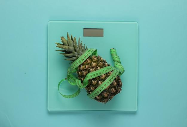 Il concetto di perdere peso. scale, ananas avvolto con nastro di misurazione su sfondo blu pastello. mangiare sano. vista dall'alto