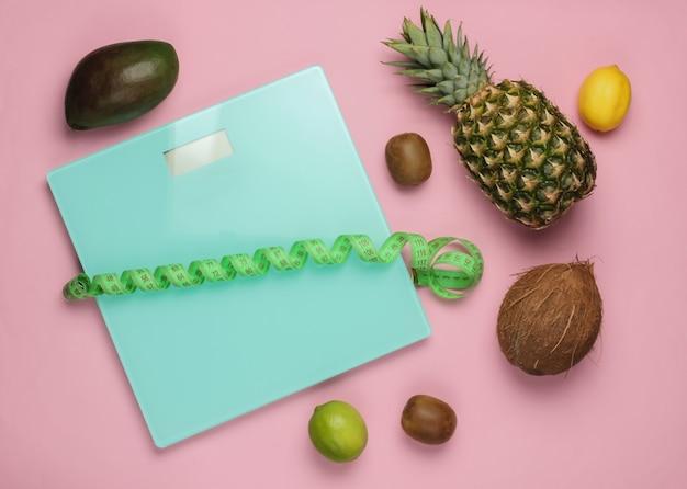 Il concetto di perdere peso. scale, righello, frutti tropicali su sfondo rosa pastello. mangiare sano. vista dall'alto