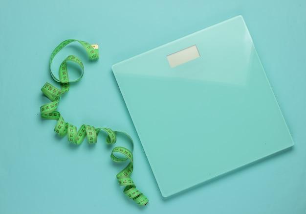 Il concetto di perdere peso. bilancia con metro a nastro su sfondo blu. mangiare sano. vista dall'alto
