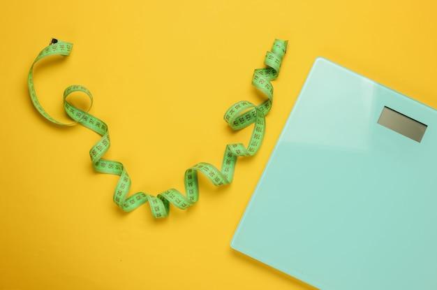 Il concetto di perdere peso. bilancia con metro a nastro su sfondo giallo. mangiare sano. vista dall'alto