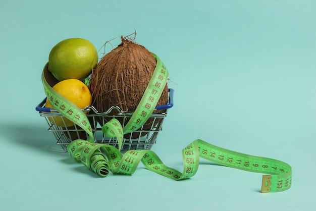 Il concetto di perdere peso. frutti tropicali e nastro di misurazione nel carrello su sfondo blu. mangiare sano. dieta della frutta. vista dall'alto
