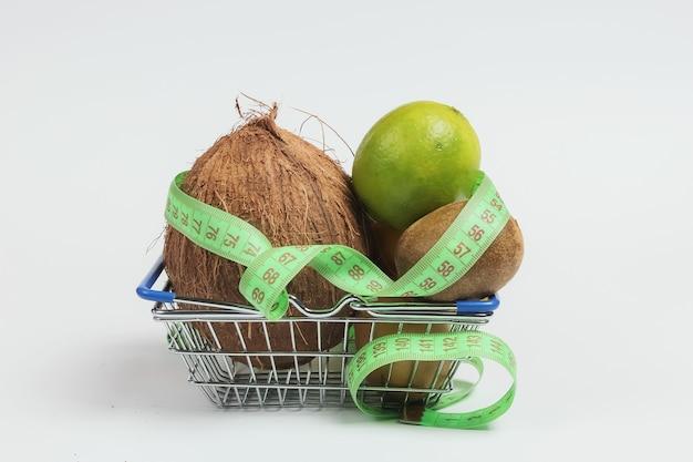Il concetto di perdere peso. frutti tropicali e nastro di misurazione nel carrello su sfondo bianco. mangiare sano. dieta della frutta. vista dall'alto