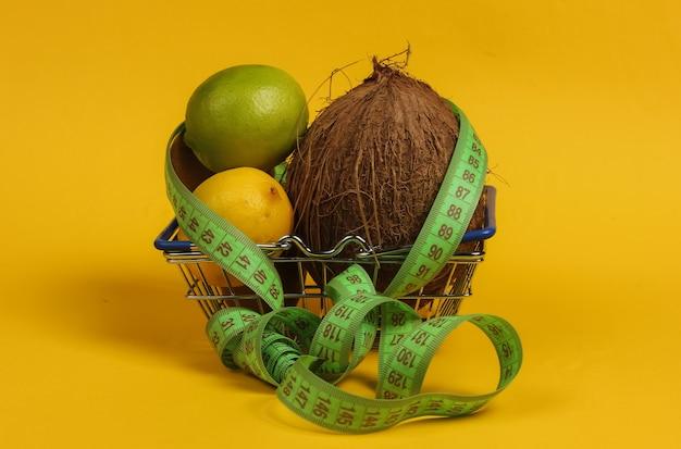 Il concetto di perdere peso. frutti tropicali e nastro di misurazione nel carrello su sfondo giallo. mangiare sano. dieta della frutta. vista dall'alto