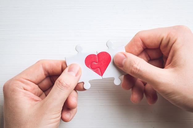 Concetto di amore da due puzzle con un cuore in mano.