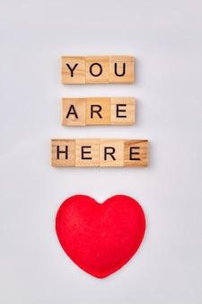 Concetto di messaggio d'amore. sei qui scritto con blocchi di legno. cuore rosso isolato su sfondo bianco.
