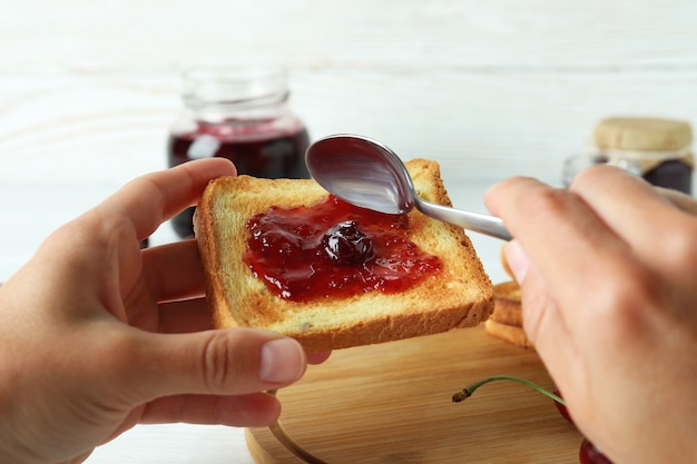 Concetto di fare un panino con marmellata di ciliegie, primo piano