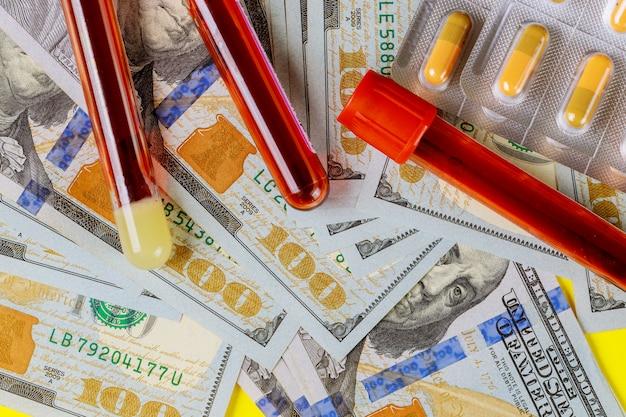 Il concetto di analisi del sangue spese mediche con pillole in blister di alluminio di banconote da cento dollari.