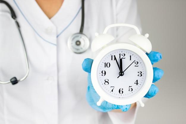 Il concetto di medicina e assicurazione sanitaria. mano del medico con la sveglia. assistenza sanitaria e paziente, il concetto di diagnosi precoce della malattia. check up sanitario annuale