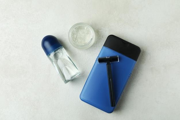 Concetto di strumenti per l'igiene maschile sulla tabella testurizzata bianca
