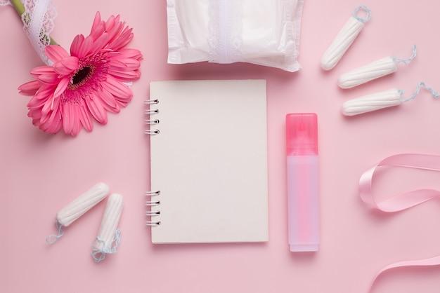Il concetto del ciclo mestruale. guarnizioni, tamponi, taccuino e pennarello.