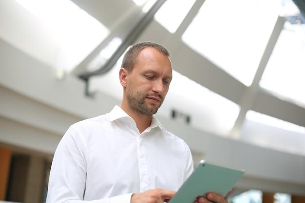 Il concetto di moderna leadership tecnologica. un ritratto semiaperto di una persona autorevole e rispettata è un leader orgoglioso che utilizza un gadget digitale sul posto di lavoro.