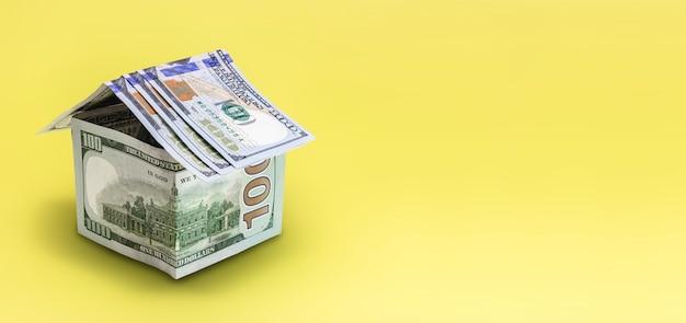 Il concetto di mutuo e locazione immobiliare e immobiliare. prestito di credito ipotecario. casa fatta di banconote da un dollaro su sfondo giallo.