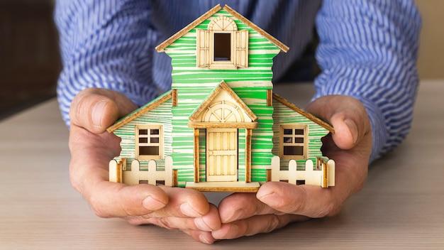 Il concetto di mutuo e locazione immobiliare e immobiliare. prestito di credito ipotecario. il layout di una casa in legno nelle mani di un uomo.
