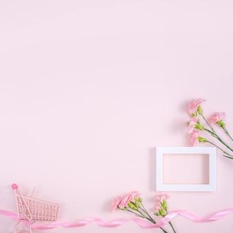 Concetto di disegno di saluto di festa della mamma con bouquet di garofani e regalo sulla superficie rosa