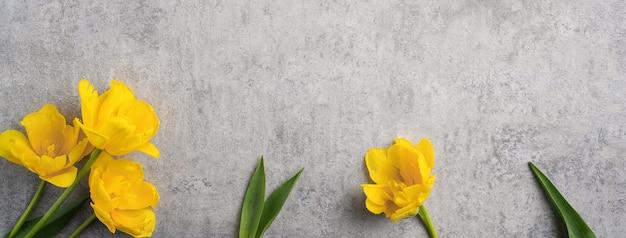 Concetto di progettazione di saluto di festa della mamma con il mazzo del fiore del tulipano giallo su fondo grigio
