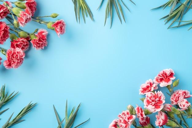 Concetto di disegno del regalo di saluto di festa di festa della mamma con il mazzo del garofano sulla superficie del tavolo blu brillante