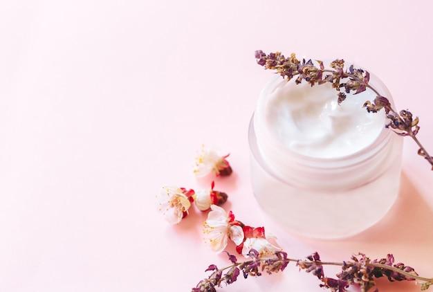 Concetto di cosmetici naturali, bellezza, cura della pelle. crema cosmetica in barattolo e fiori. vista dall'alto e copia spazio.