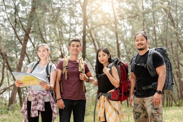 Concetto di turismo naturalistico e trekking, un gruppo di quattro backpackers asiatici maschi e femmine. guarda dritto nella telecamera pianificazione di un'escursione nella foresta.