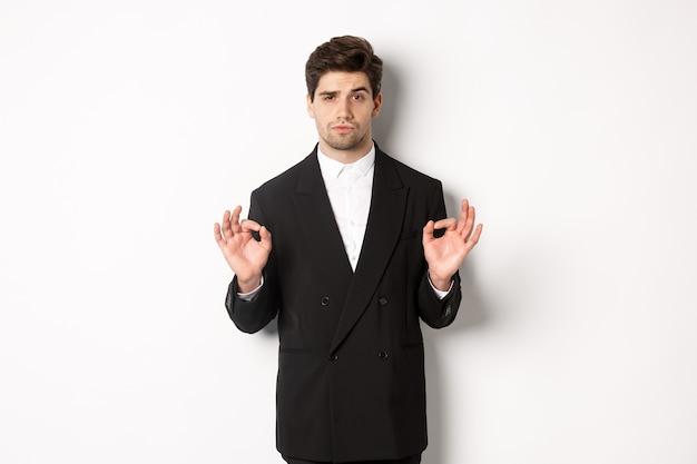 Concetto di festa di capodanno, celebrazione e stile di vita. ritratto di un bell'uomo fiducioso in abito nero, che mostra un segno ok e approva qualcosa, in piedi su sfondo bianco