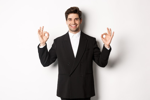 Concetto di festa di capodanno, celebrazione e stile di vita. ritratto di un bell'uomo attraente in abito nero, sorridente e che mostra segni ok, approva e consiglia qualcosa, sfondo bianco