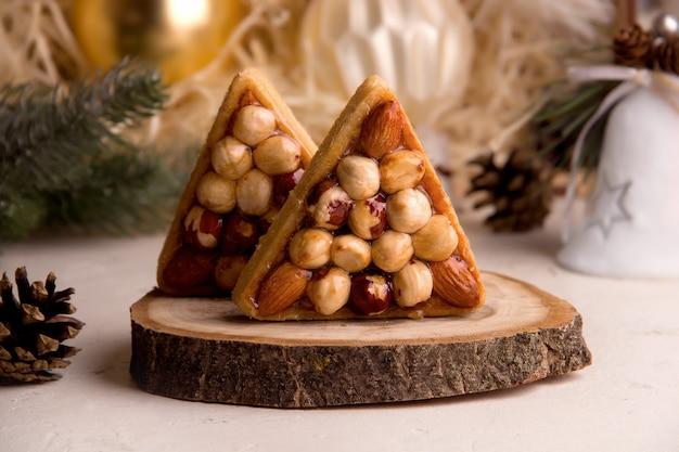 Il concetto di ricette di biscotti di capodanno. biscotti dolci triangolari con noci sullo sfondo di un albero di natale