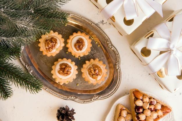 Il concetto di dolci di capodanno. biscotti con noci e panna su un vassoio. vista dall'alto