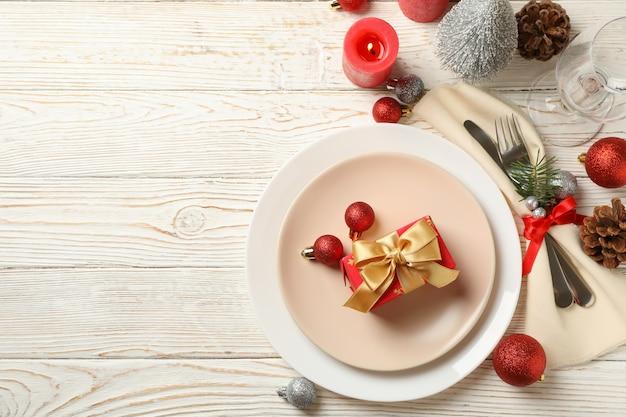 Concetto di impostazione della tavola del nuovo anno con confezione regalo sulla tavola di legno