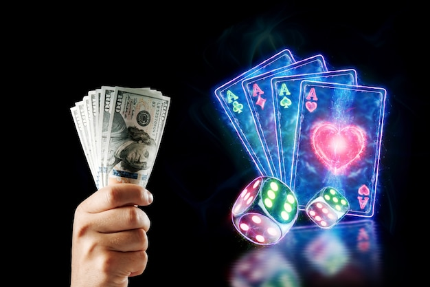 Concetto per casinò online, gioco d'azzardo, giochi di denaro online, scommesse. la mano di un uomo tiene i dollari su uno sfondo di carte da poker al neon e dadi su uno sfondo nero.